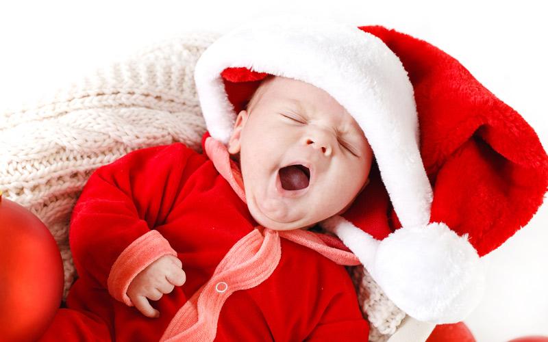 Zívající miminko ve vánočním oblečení