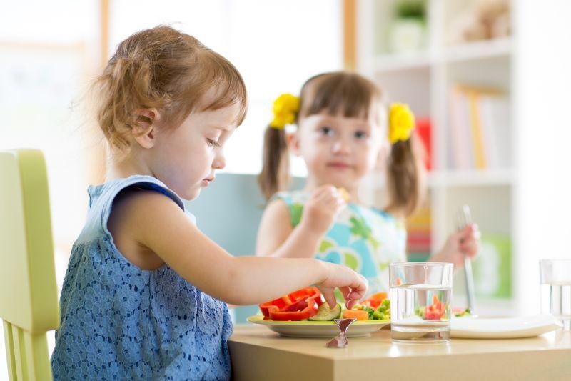 Chlapeček a holčička jedí zeleninu