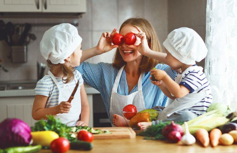 Šťastná matka se hraje v kuchyni s dětmi