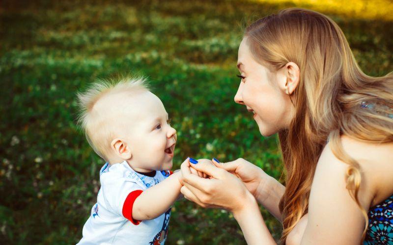 Usmívající máma s dítětem v parku